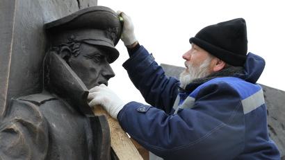 Сергей Сюхин очищает элементы памятника после перевозки